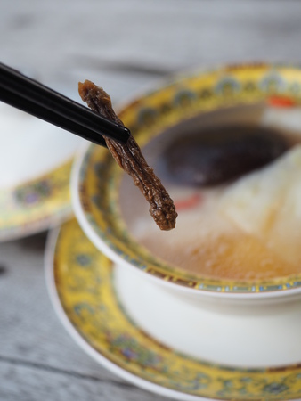 Holding Black Chopsticks with Cordyceps Chinese herbs with blur background of cleared soup of fresh fish maw in royal yellow style bowl. Stock Photo