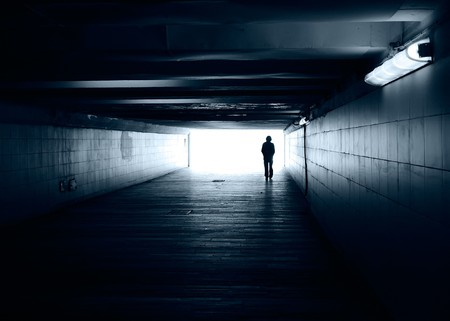 alone in the dark: Lonely silhouette in a subway tunnel