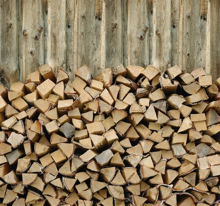 Pile of firewood against old wooden fence photo