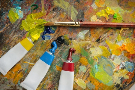 Palette with paint brush and tubes of oil paint photo