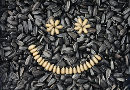 black seeds: Smile made with peeled sunflower seeds over sunflower seeds background Stock Photo