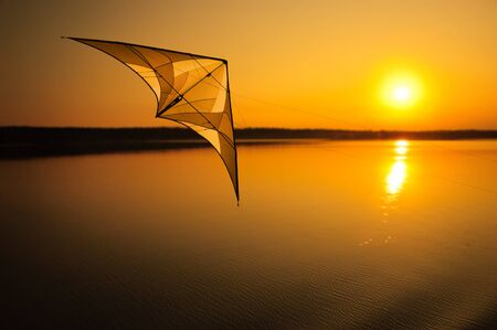 Kite flying over peaceful lake at sunset Stock Photo - 9652119