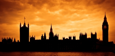 parliament building: London, UK. Silhouette of the Houses of Parliament and Big Ben across River Thames at sunset Stock Photo
