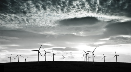Silhouettes of wind turbines against dramatic clouds