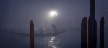 Gondola in a thick fog during nightfall in Venice, panoramic shot
