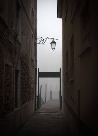 alone in the dark: Wooden pier at the end of an alley in Venice Stock Photo