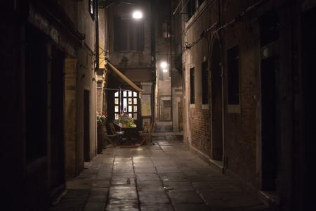 acogedor restaurante en un callejón en la noche en Venecia, Italia