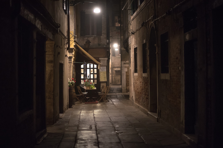 Cozy restaurant in an alley at night in Venice, Italy