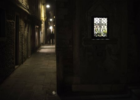 house windows: Brightly lit window in a narrow alley of Venice at night