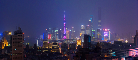 huangpu: SHANGHAI, CHINA - MARCH 19, 2015: Famous Shanghai skyscrapers of Pudong financial district at night. Wide panorama shot from the roof of a building across the river.