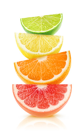 Isolated citrus fruits wedges. Pieces of grapefruit, orange, lemon and lime on top of each other isolated on white background