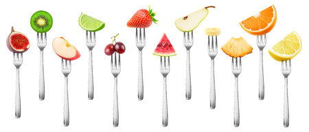 12 isolated fruit pieces. Cut fig, apple, kiwi, lemon, grape, orange, lime, strawberry, watermelon, banana, pineapple and pear on a steel dessert fork isolated on white background