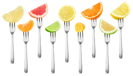 Isolated citrus pieces collection. Grapefruit, lemon, orange, lime and kumquat fruits on a dessert forks isolated on white background