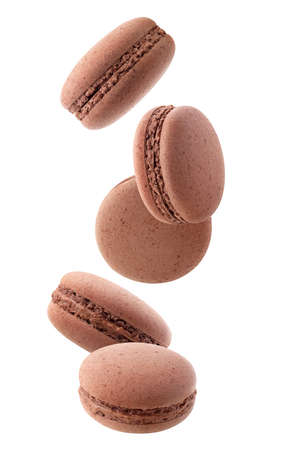 Isolated macaroons. Five chocolate macaroons falling down over white background