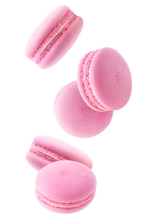 Five falling pink macaroons isolated on white background
