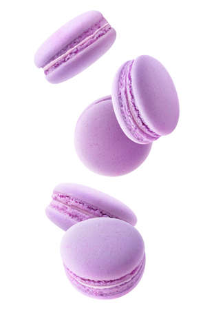 Five falling blueberry or blackberry macaroons isolated on white background