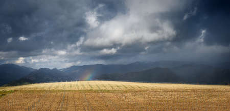 End of the rainbow, landscape panorama with dramatic sky. Thunderstorm clouds over leafless vineyard in early spring and tiny piece of rainbow, with distant mountains on background Standard-Bild