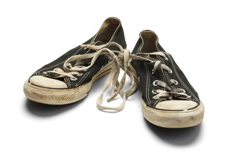 tearing down: Old Dirty Worn Pair of Canvas Shoes With Knoted Shoe Laces Isolated on White Background.