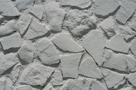 White stone wall, big pieces of stone, all paint white. photo