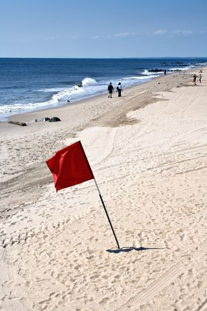 Red flag on the beach, no swimming no bathing. photo