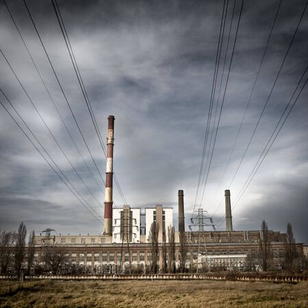 clody: Power plant with high chimneys. Visible cables  on clody sky. Stock Photo