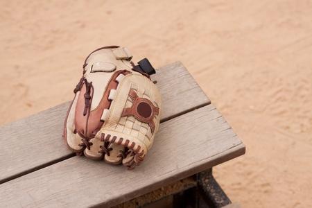 guante beisbol: Cuero guante de b�isbol en el banco de madera