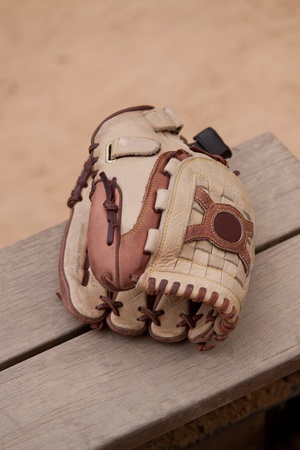 Leather baseball glove on the wooden bench Stock Photo - 11959597