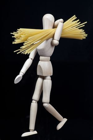 wooden model figure walking with spaghetti on his shoulder photo