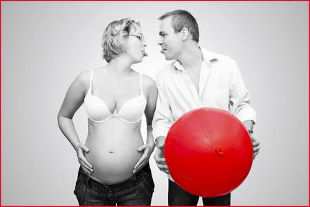 pregnant woman and her husband witn red balloon Stock Photo