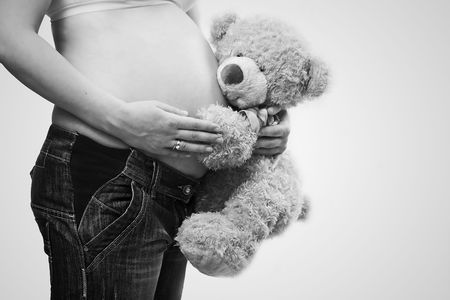adult toys: pregnant belly being hugged by cute teddy bear Stock Photo
