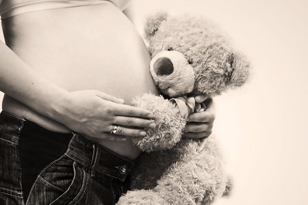 pregnant belly being hugged by cute teddy bear Stock Photo