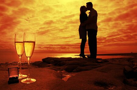 silhouette of kissing couple in the sunset Stock Photo