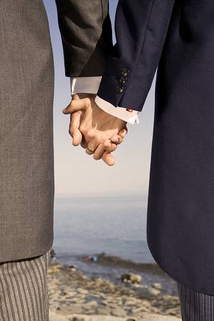 honeymoons: two men in suits holding hands on the sea side Stock Photo