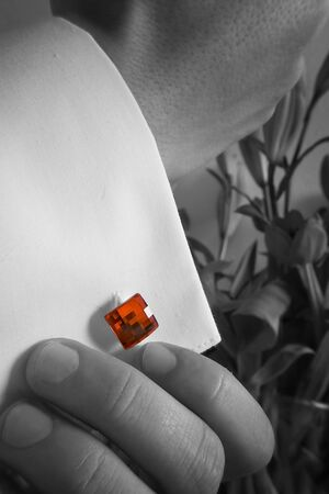 cufflink: groom pin his red cufflink to the sleeve