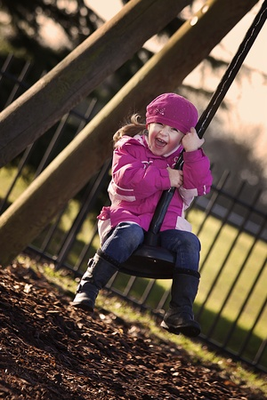 happy girl swinging on the swing in park photo
