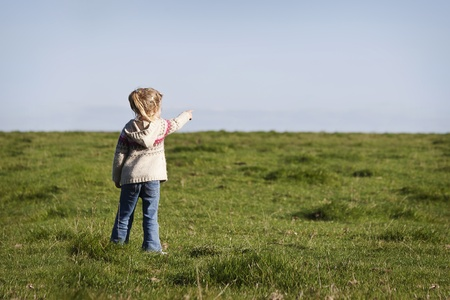 little girl pointing something in the horizont photo