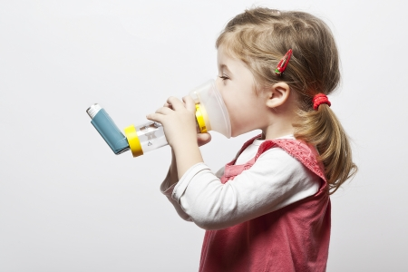 asthma: little girl doing inhlation using her inhaler
