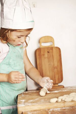 little girl in cook outfit cooking delicious dinner