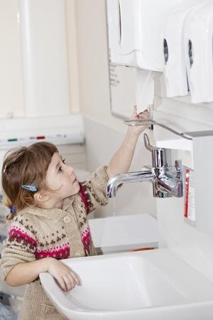 lavare le mani: bambina con mani pulite, afferrando il tovagliolo di carta
