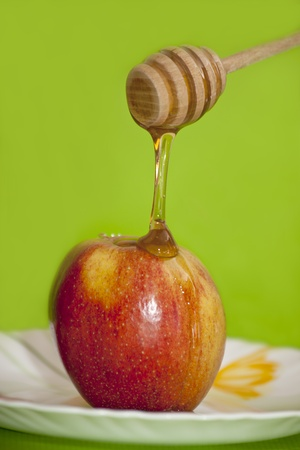 honey dripping on an apple from wooden honey spoon