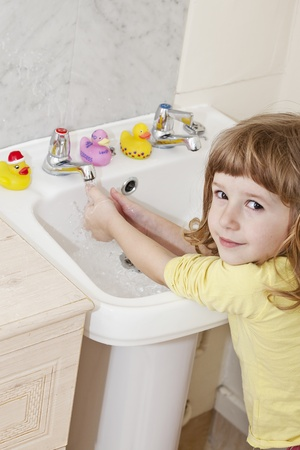little girl washing her hands in white sink Stock Photo