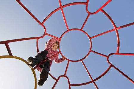 little girl climbing on a metal play frame Stock Photo - 9179743