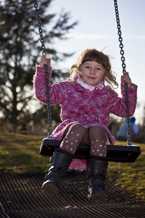 smiling little girl swinging on the swing Stock Photo - 9179751