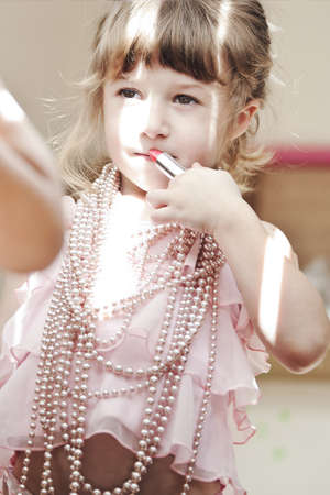 little girl uses her mums pink  lipstick Stock Photo - 9179748