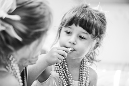 little girl putting on lipstick in front of the mirror photo
