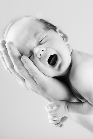 little crying baby on the fathers hand in black and white Stock Photo