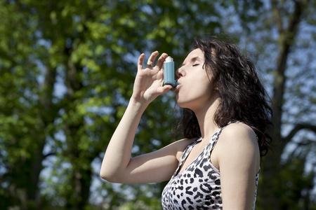 arbol de problemas: mujer con inhalador sobre fondo verde de �rboles Foto de archivo
