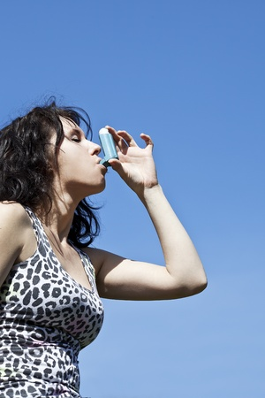 woman useing inhaler on blue sky background