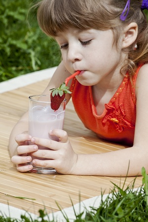 girl drinking fresh strawberry juice from glass Stock Photo - 9448429