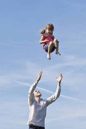 dad throwing his daughter up to the sky Stock Photo